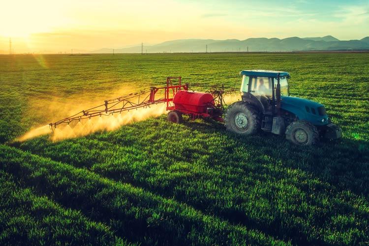tractor spraying field - farm is protected by CrossRoads farm insurance in Iowa