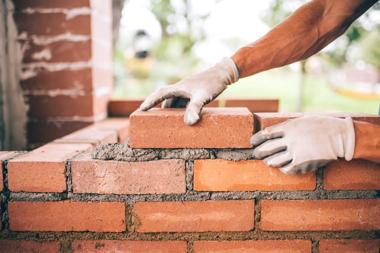 Construction worker building brick structure - contractor company protected by CrossRoads insurance services