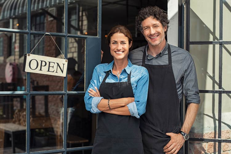 small business owners stand in front of their shop smiling